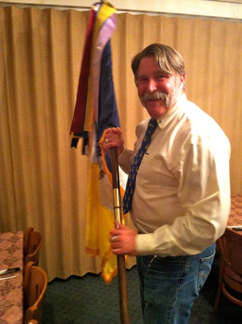 Registrar Kurt Lawson assists with the SAR flag and ribbons at the conclusion of the  May Membership Meeting.