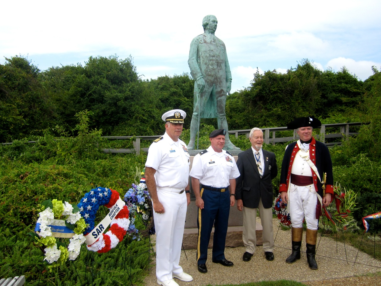 Virginia State SAR President Reverdy Wright, Captain Christopher Melhuish, USN Ret. (in period attire) join in with the Commanding Officer and Executive Officer of Fort Story/Joint Expeditionary Base in front of the Admiral deGrasse Statue
