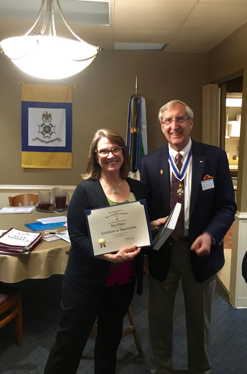 President Ken Hawkins presents Lin Olsen from the Great Bridge Battlefield and Waterways History Foundation Museum and Visitor's Center with a Certificate of Appreciation for her program presentation.