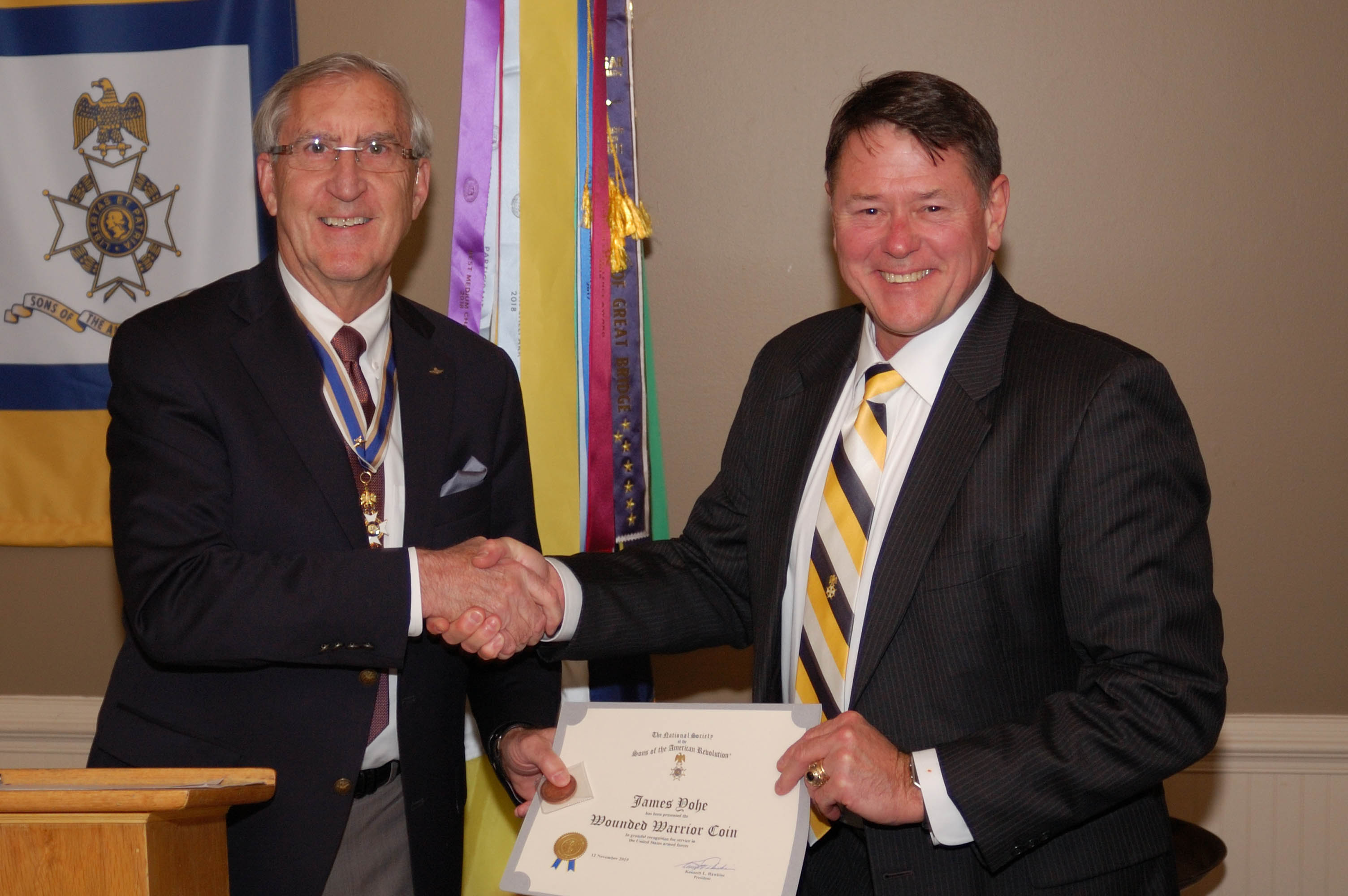 Chapter Registrar Jim Yohe receiving Wounded Warrior certificate and coin from President Ken Hawkins